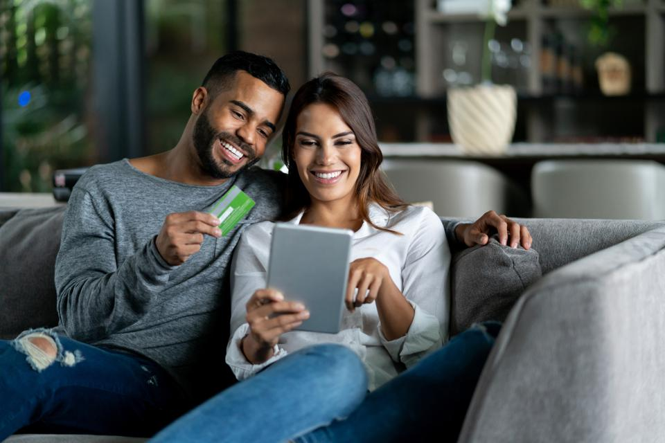 Beautiful adult couple at home relaxing on couch shopping online while man holds credit card both smiling