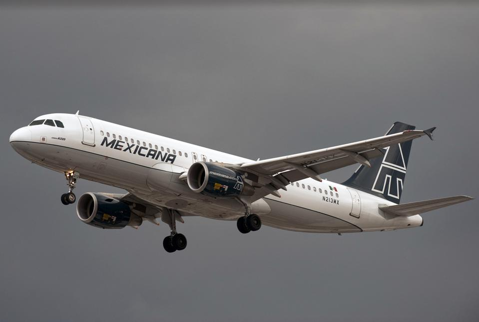 A Mexicana airlines plane flies over Mex