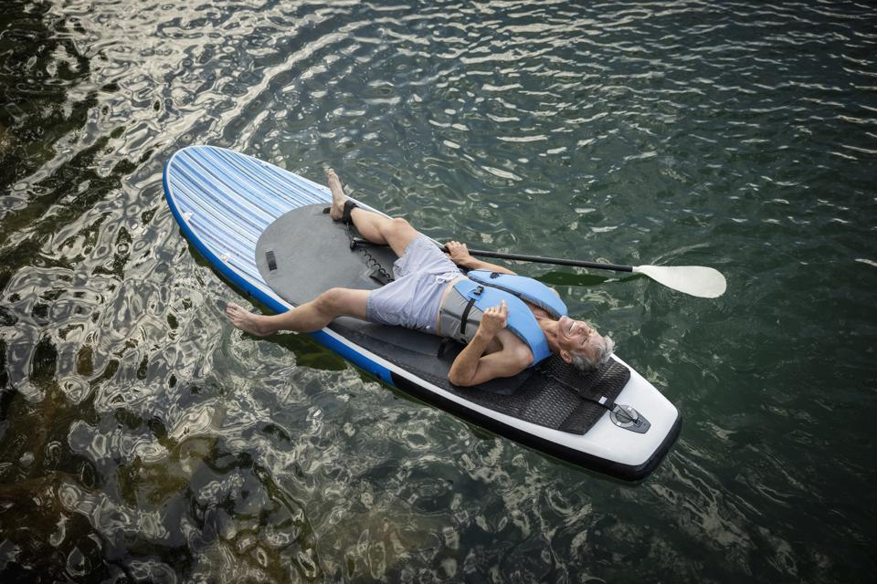Serene mature man relaxing, laying on paddleboard on lake