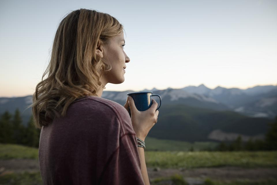 Thoughtful, serene woman drinking coffee and looking at mountain view, Alberta, Canada