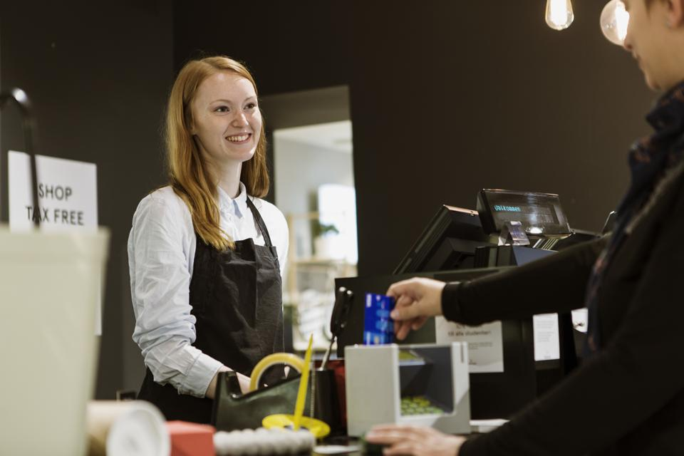 Smiling female owner looking at customer while standing in checkout counter of store