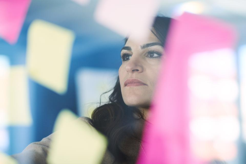 Female mature engineer reading adhesive notes seen through glass in office