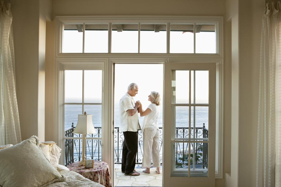 Senior couple holding hands face to face on balcony overlooking ocean
