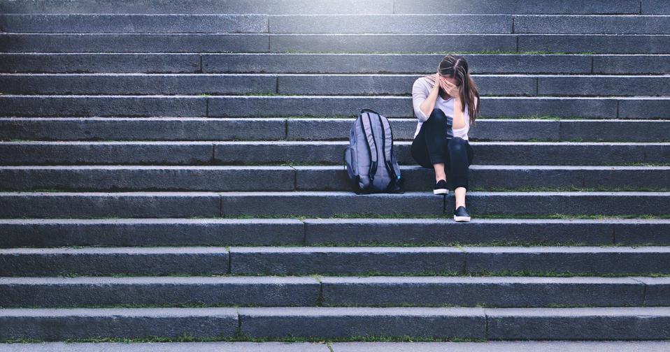 Bullying, discrimination or stress concept. Sad teenager crying in school yard. Upset young female student having anxiety. Upset victim of abuse or harassment sitting on stairs outdoors.