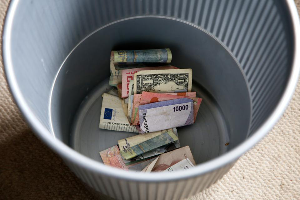 A plastic bin filled with money from around the world.
