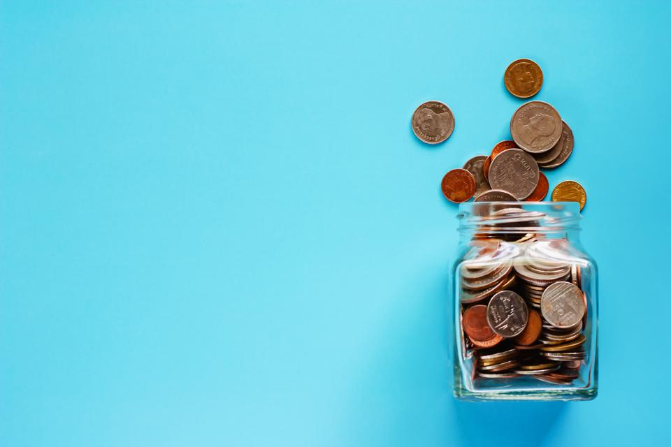 Coins in glass jar and outside, Thai currency money on blue background for business and finance concept