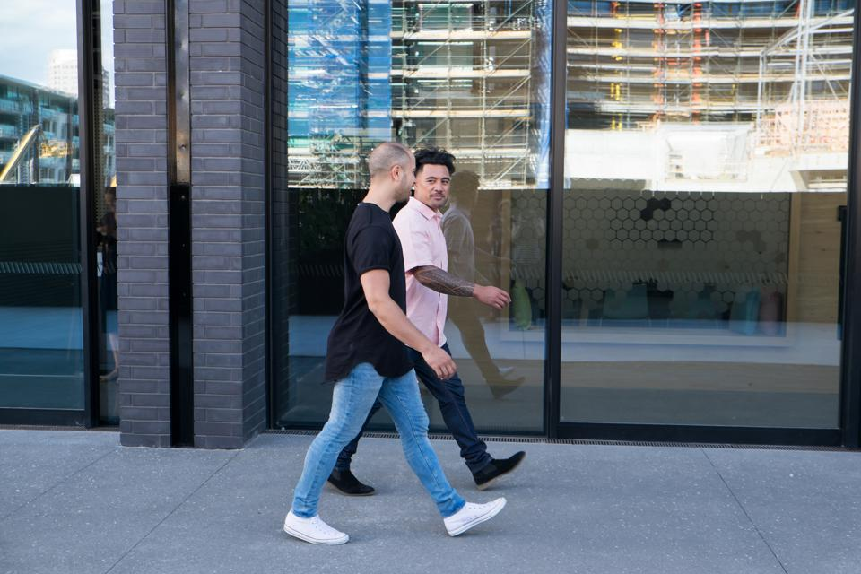 Two men walking and talking outside in front of a glass office building.