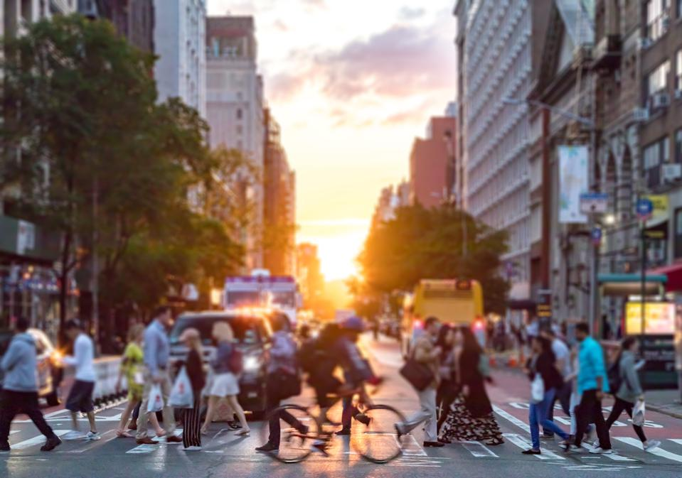 Crowds of people cross a busy intersection on 23rd Street and 6th Avenue in Manhattan with the colorful sunset background
