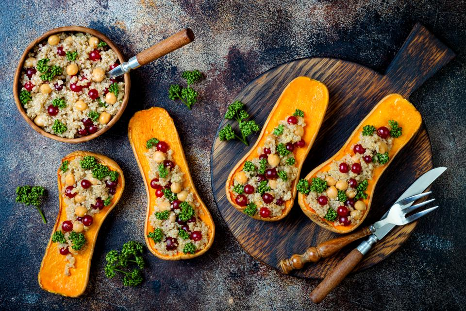 Stuffed butternut squash with chickpeas, cranberries, quinoa cooked in nutmeg, cloves, cinnamon. Thanksgiving dinner recipe. Vegan healthy seasonal fall or autumn food