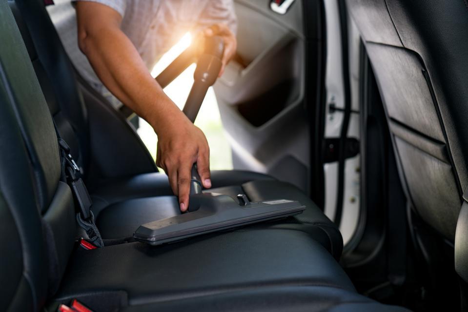 Section médiane de l'homme avec un aspirateur dans le siège d'auto