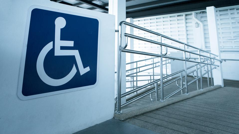 Concrete ramp way with stainless steel handrail with wheelchair symbol sign.