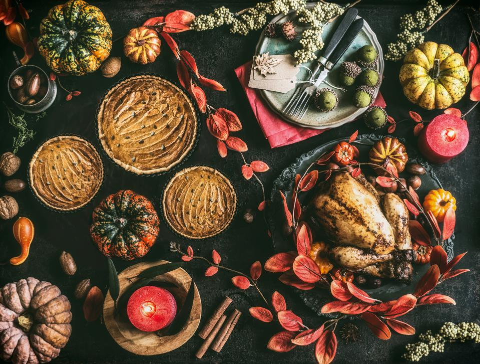 Thanksgiving day dinner table with pumpkin pie, roasted turkey and festive autumn decoration and candles