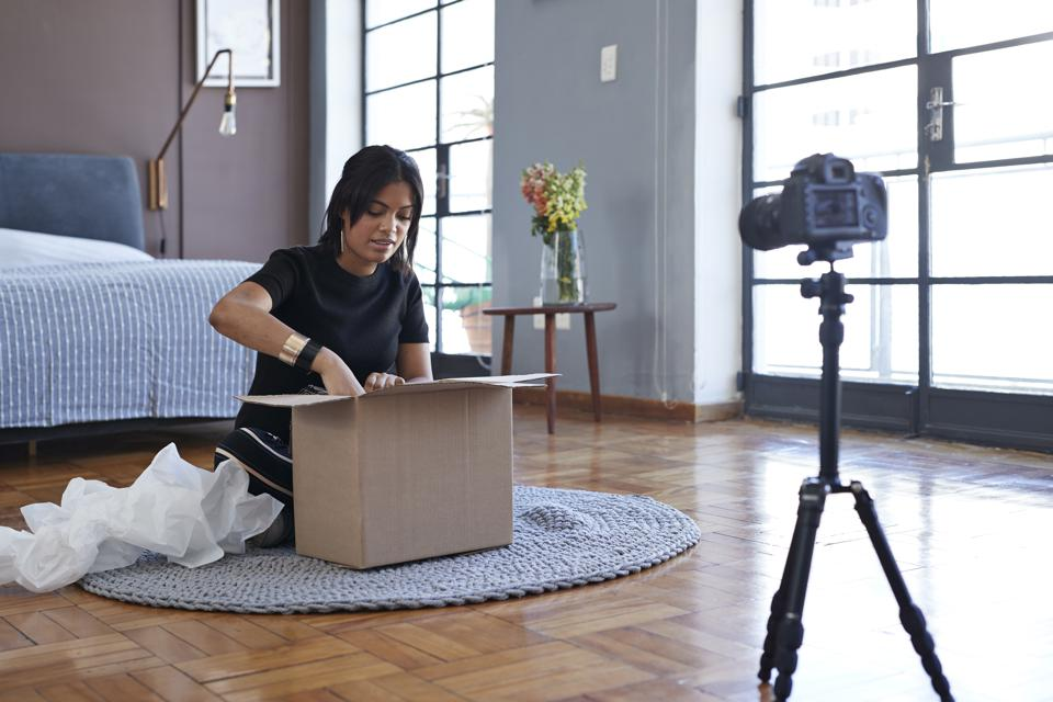 Female influencer doing ″unboxing″ video from home