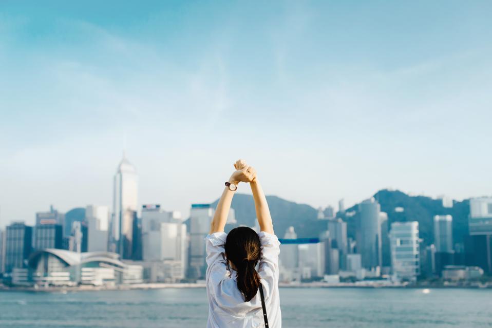 Vue arrière du voyageur femme profitant de son temps à Hong Kong, en prenant une profonde respiration avec les mains levées contre le port de Victoria et sur les toits de la ville