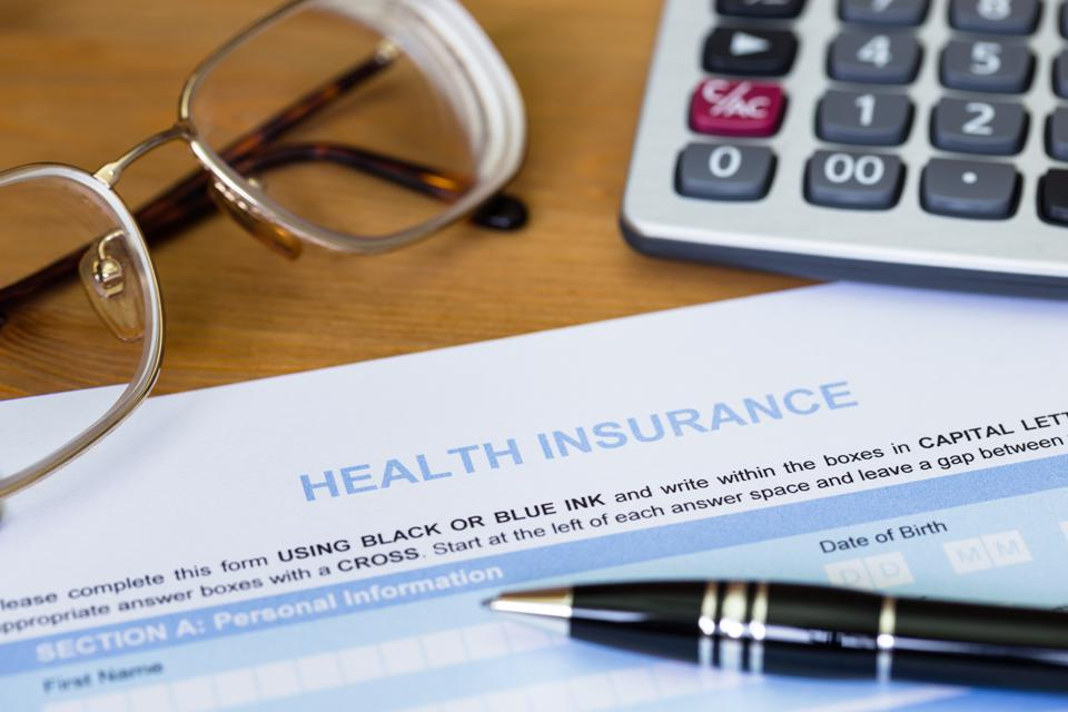 Health insurance application form with pen, calculator, and glasses