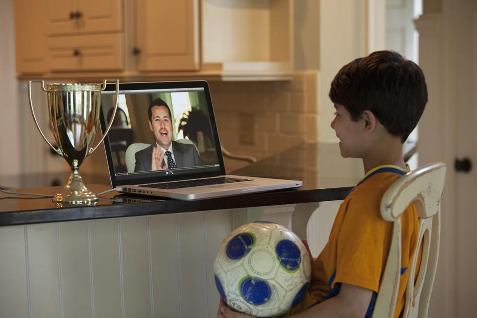 Hispanic boy with soccer ball watching video on laptop