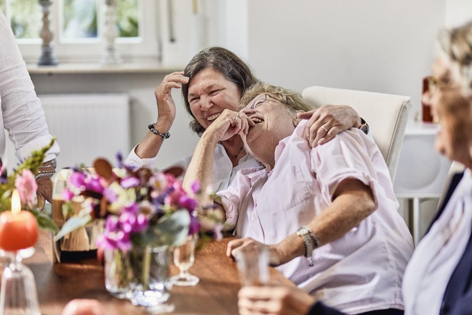 Carefree senior friends drinking champagne on a celebration at table