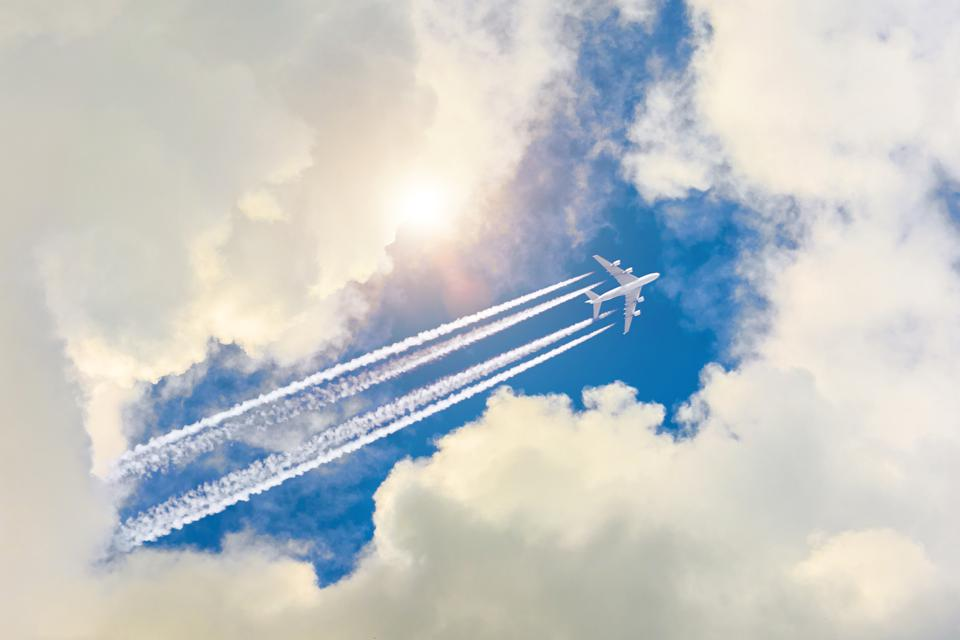 Airplane flies high in the sky, a journey through the clouds and a sunny glare.