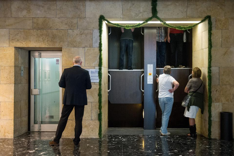 People stand in front of the Paternoster elevator in the city hall of Stuttgart, Germany.