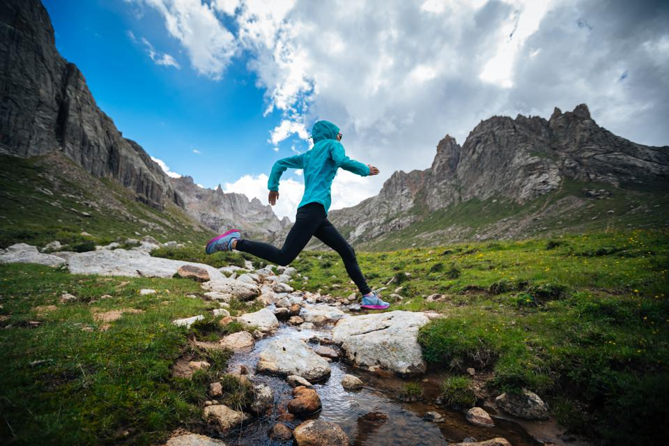 Woman trail runner jumping over samll river on beautiful mountains