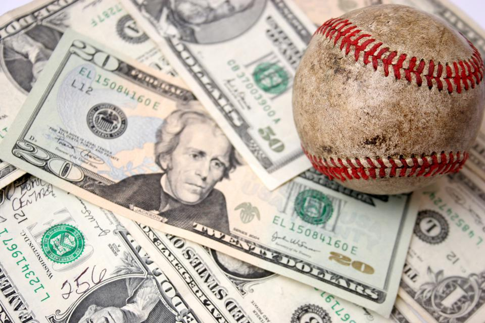 A dirty baseball sitting on a pile of money