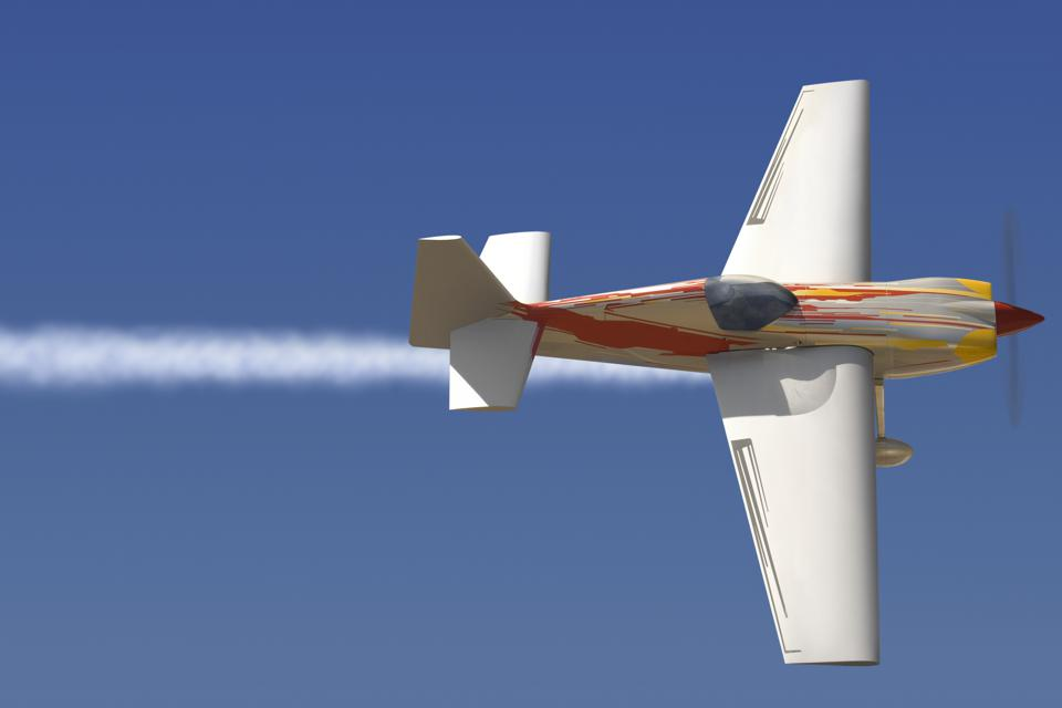 A small plane in mid flight writing a line through the sky