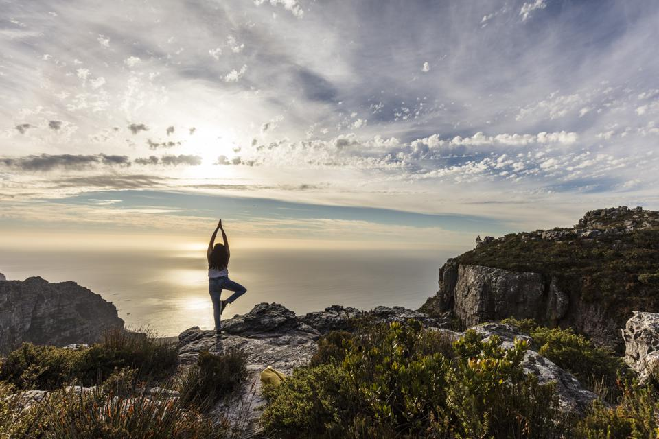 South Africa, Cape Town, Table Mountain, woman doing yoga on a rock at sunset