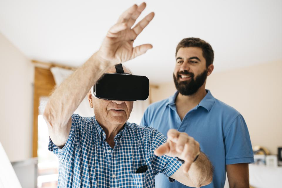 Senior man using Virtual Reality Glasses at home while his adult grandson watching him