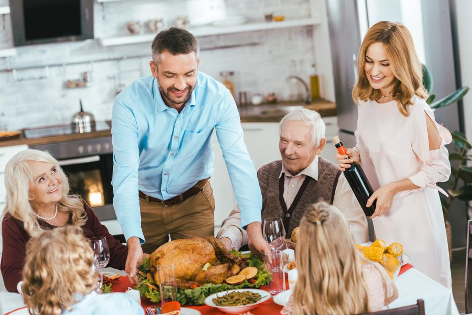 smiling family with turkey celebrating thanksgiving day at home