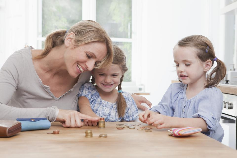 Germany, Munich, Mother with daughters (4-7) counting stack of coins