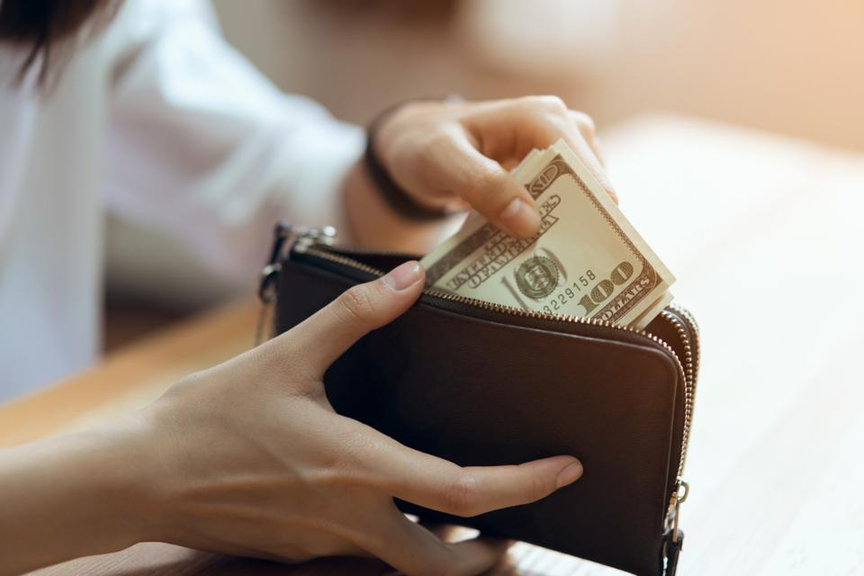 Midsection Of Woman Putting Paper Currencies In Purse