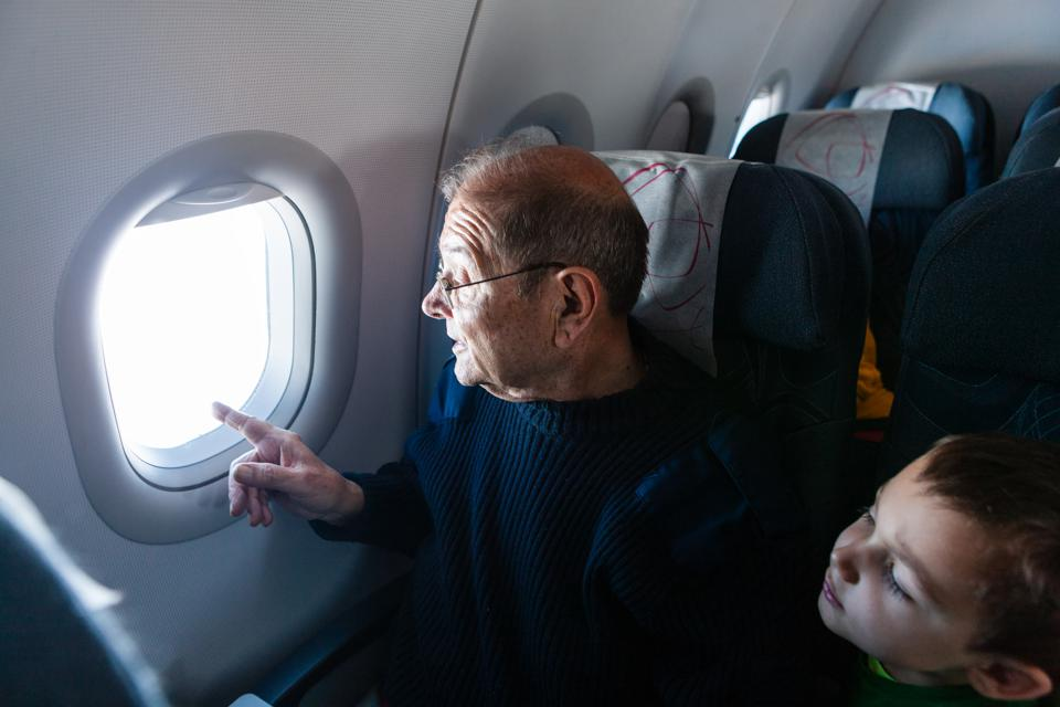 Grandfather and grandson looking through airplane window COVID-19 Coronavirus