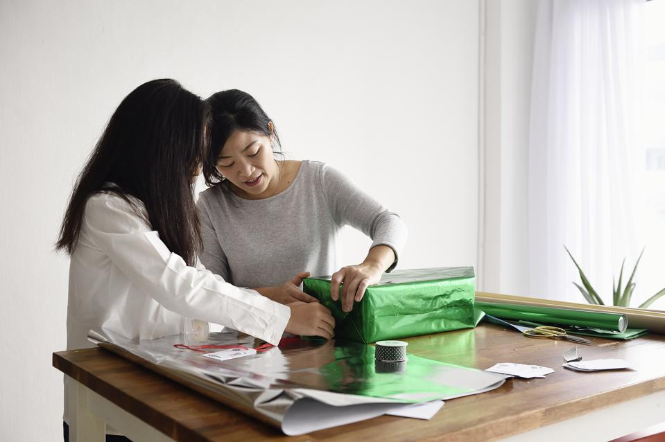 Woman wrapping Christmas presents with her teenage daughter
