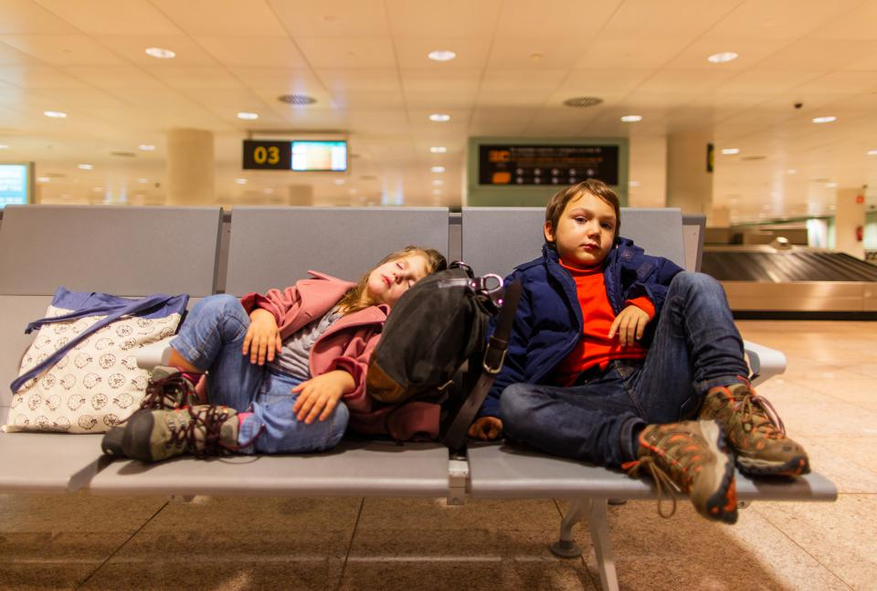 Toddler siblings relaxing in airport waiting hall