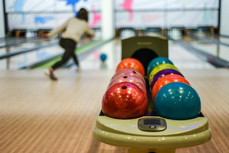 A detail shot of colourful bowling bowls while a female...