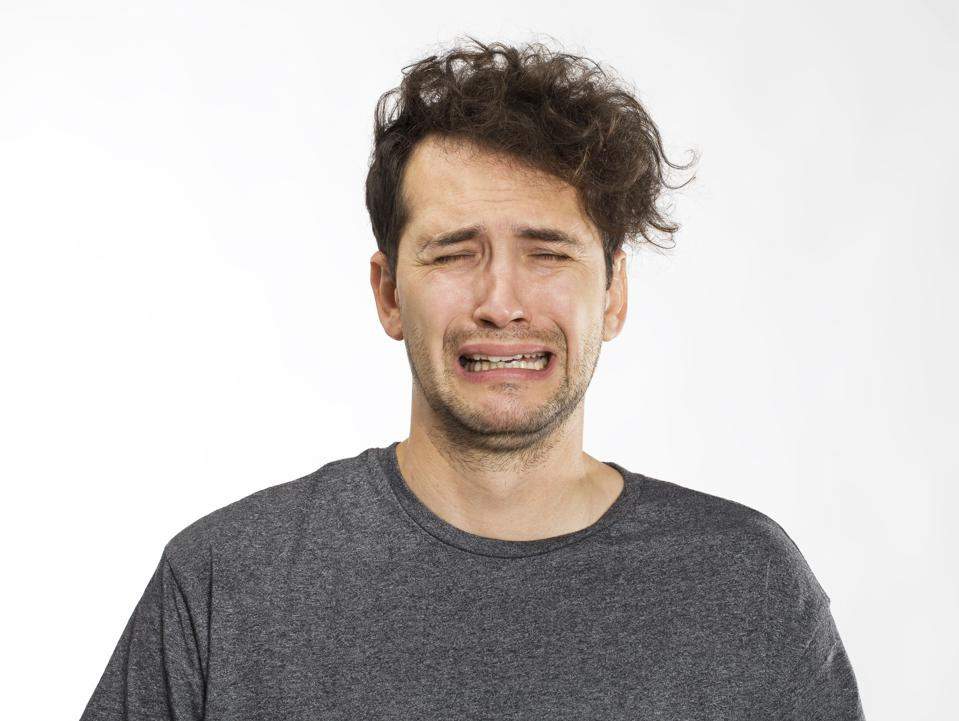Frustrated and worried young man portrait in grey t-shirt