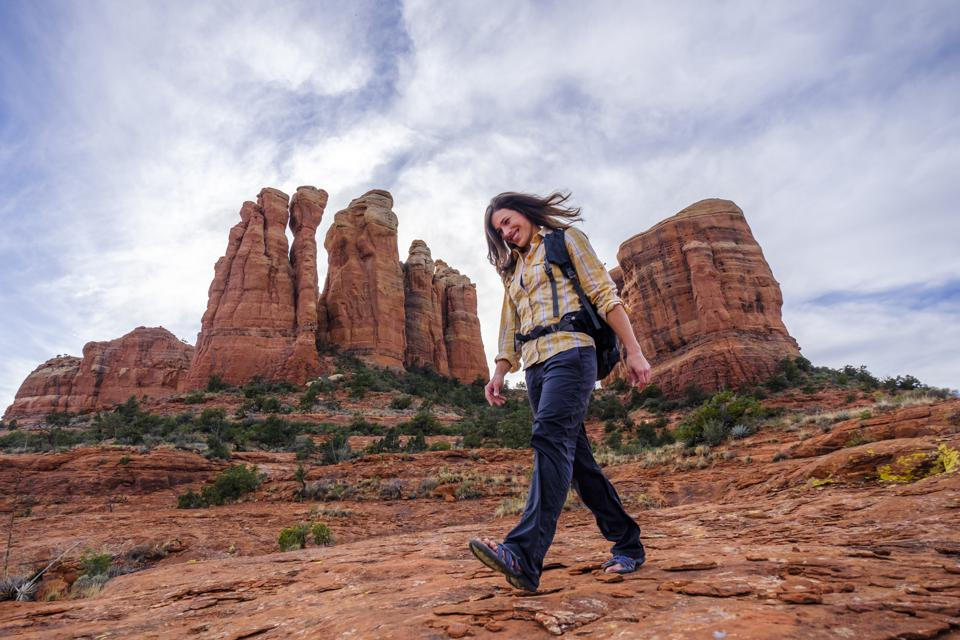 Female hiker walking down rocks at Cathedral Rock, Arizona, United States