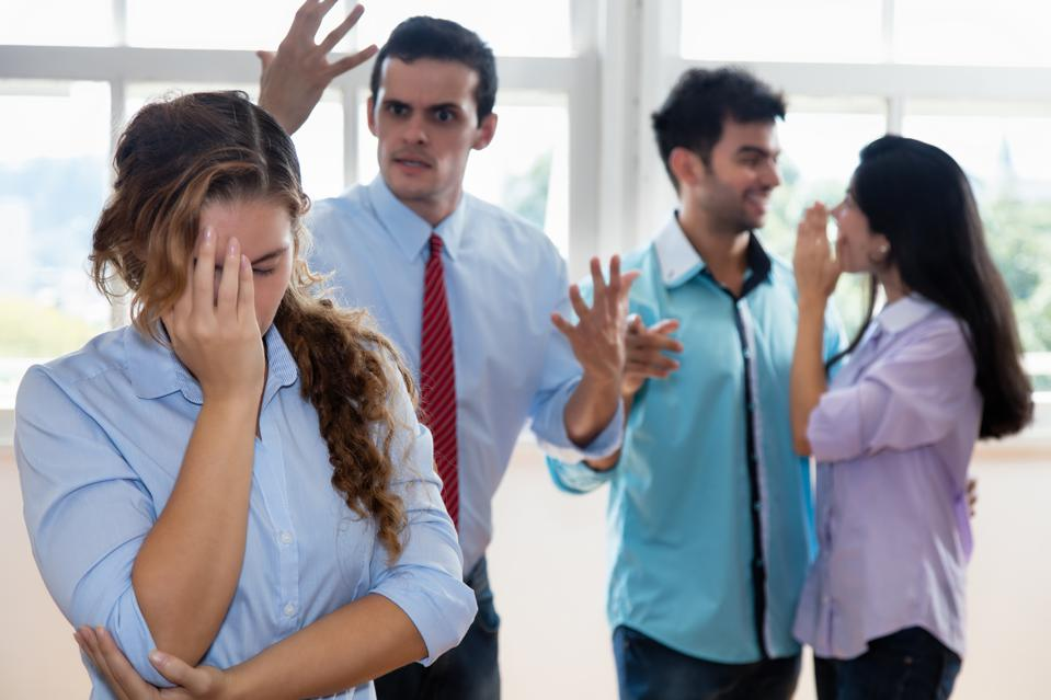 Businessman and colleagues bullying employee