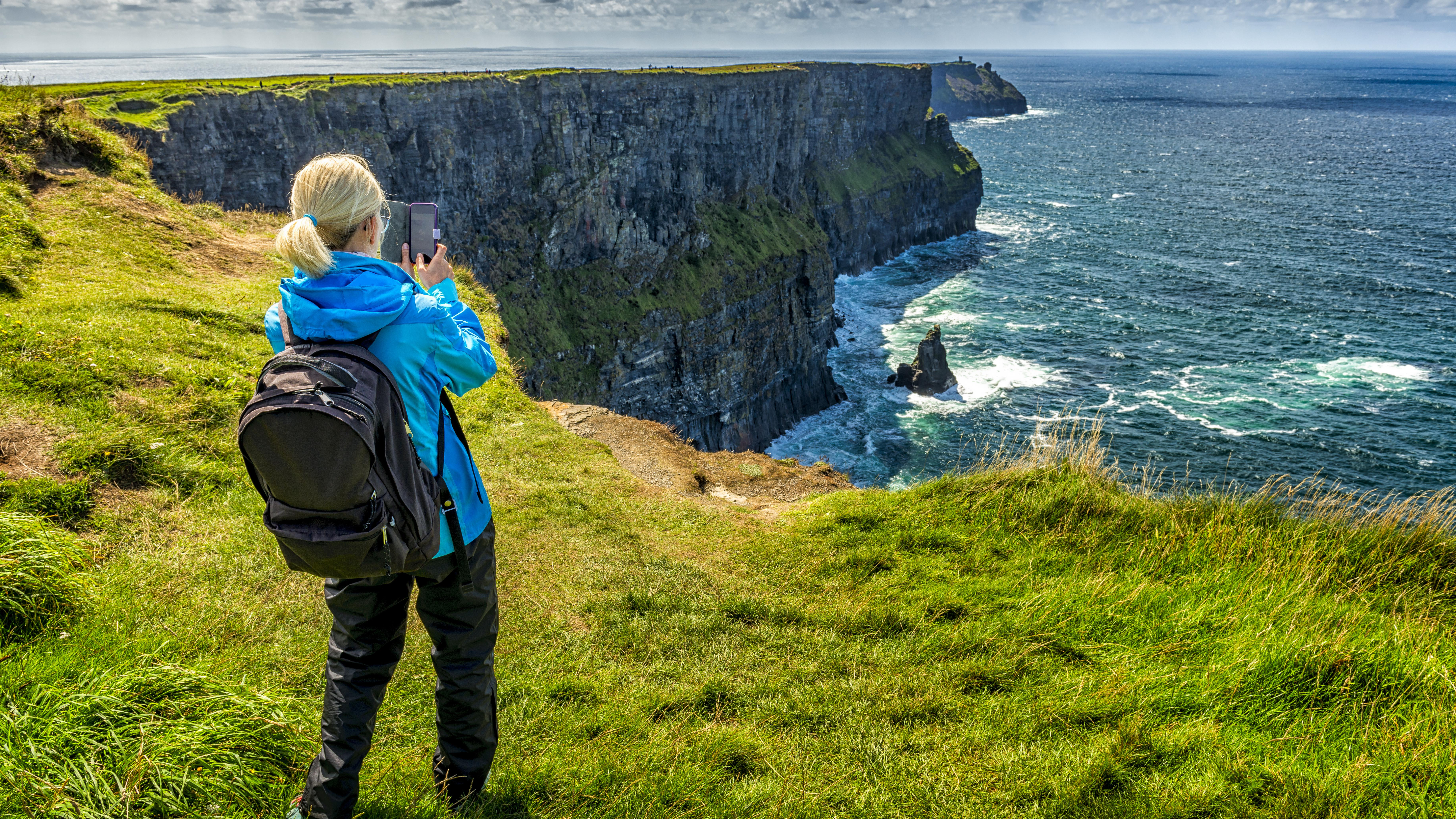 woman taking photo of Cliffs of Moher in Ireland