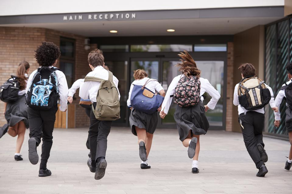 Group Of High School Students Wearing Uniform Running Into School Building At Beginning Of Class