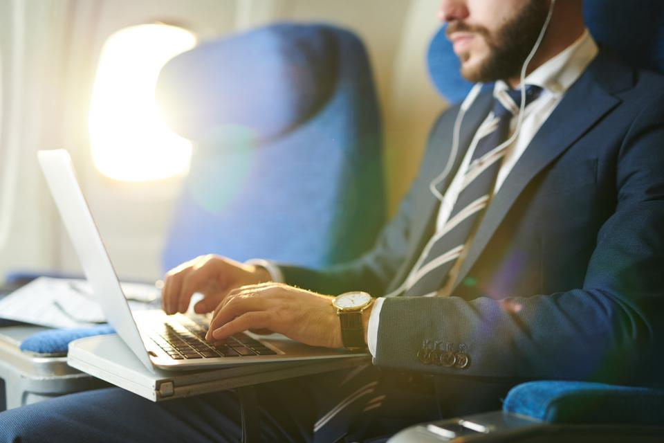 Businessman Using Laptop in Plane Closeup