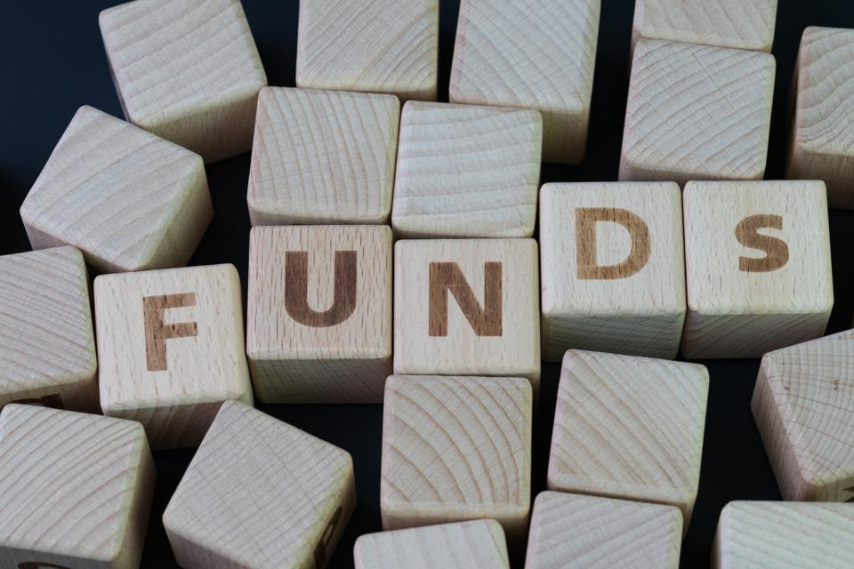Mutual funds, investment asset selection by performance concept, cube wooden block with alphabet combine the word abbreviation FUNDs on black chalkboard background