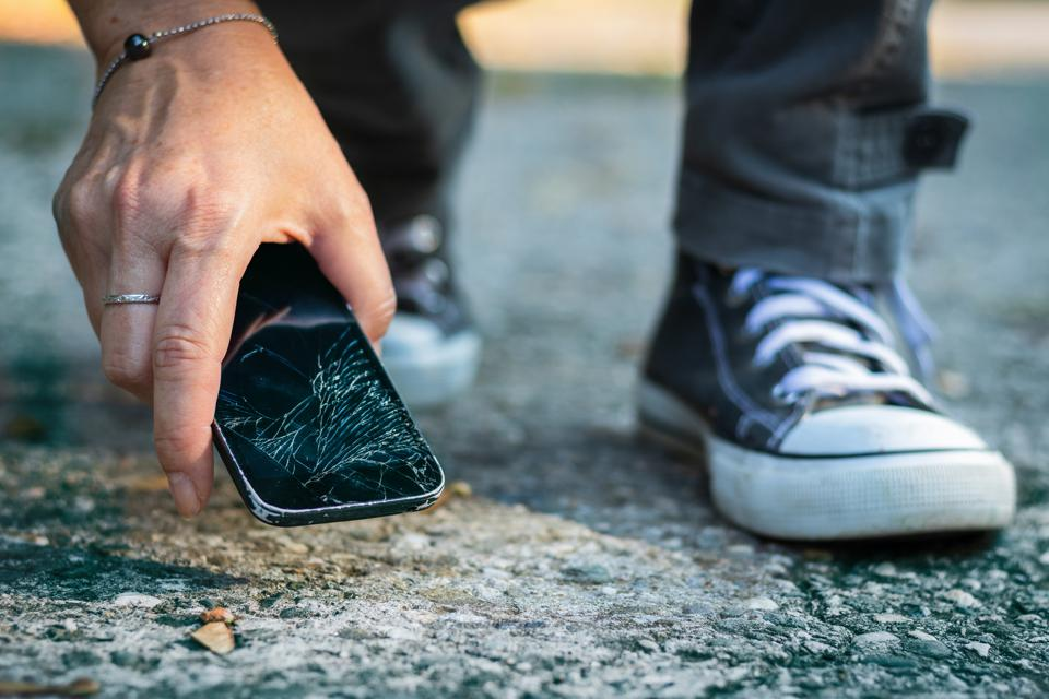 Broken smartphone on the ground.