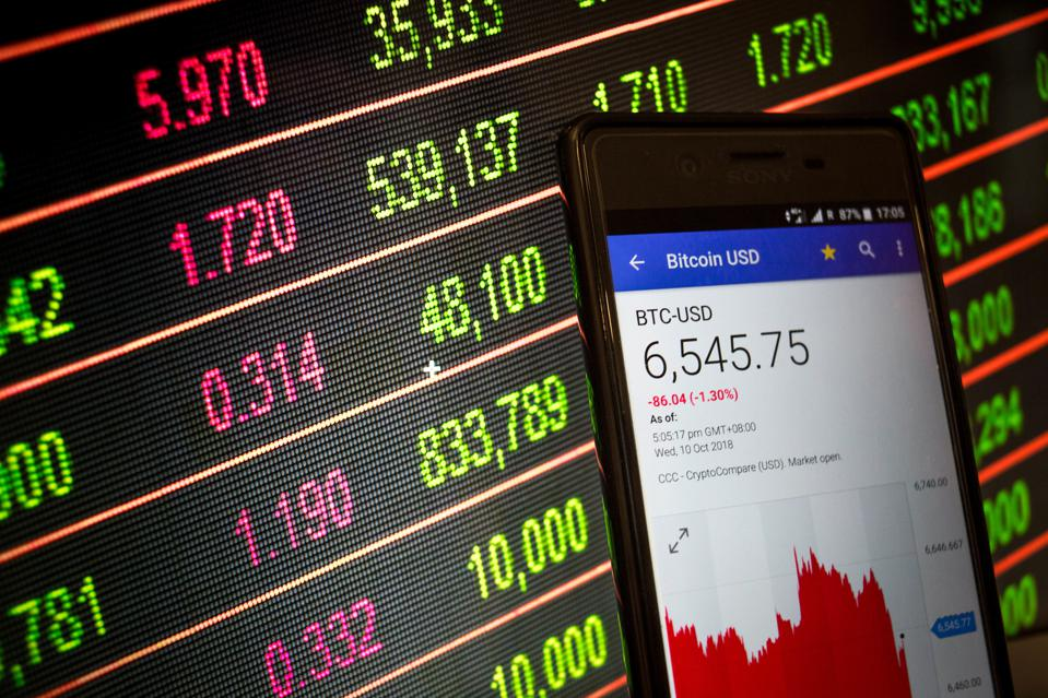 A smartphone displays the Bitcoin USD market value on the