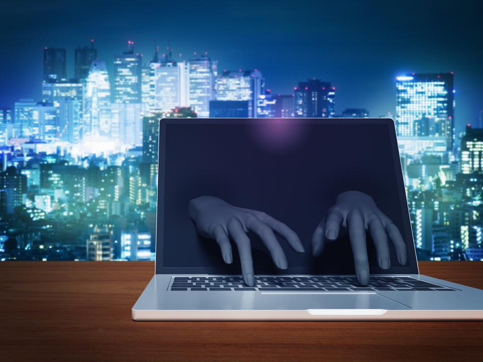 Hacker's hand to operate keyboard from laptop computer monitor