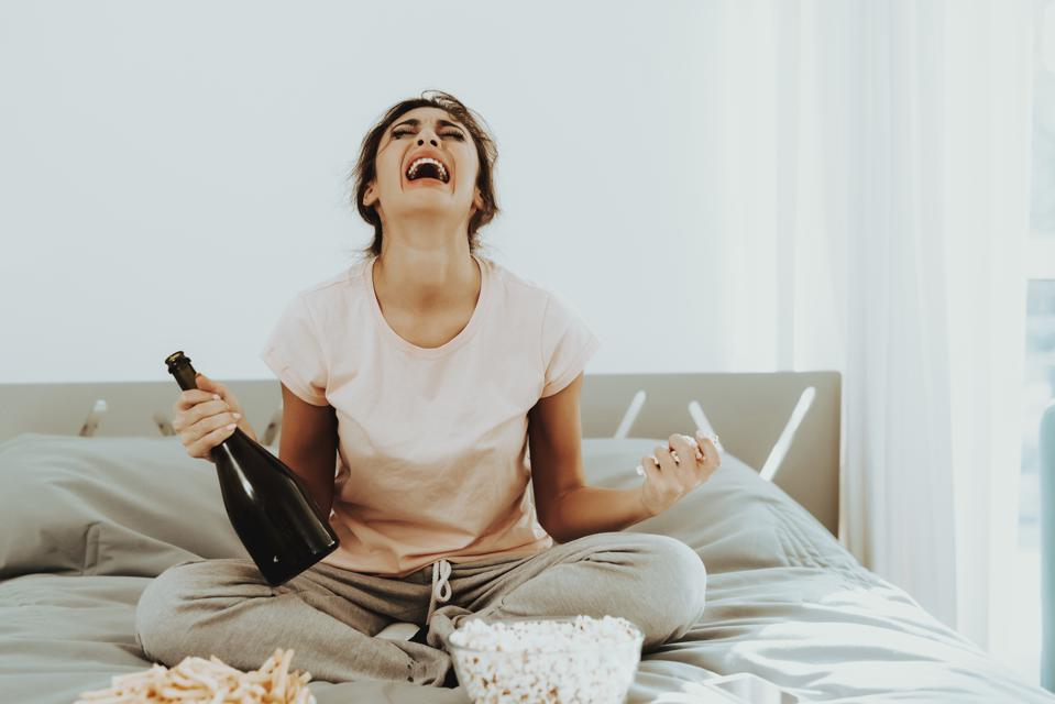 Crying Woman Sits On Bed With Bottle Of Champagne.