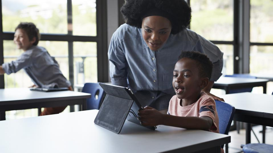 Teacher assisting boy working tablet at school