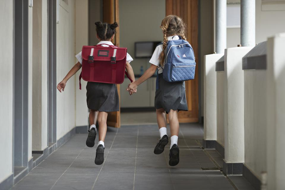 Schoolgirls running hand in hand on the isle of school and laughing