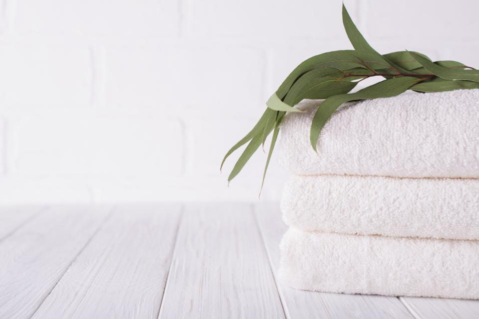 Stack of three white fluffy bath towels with eucalyptus branch. Copy space