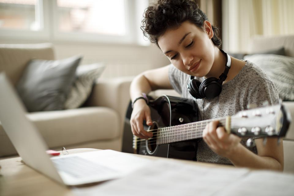Smiling girl playing a guitar at home